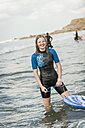 Portrait of smiling teenage girl with surfboard wearing wet suit - PAF001048
