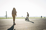 Germany, Berlin, Tempelhof Field, young adults skating with longboards - FX000085