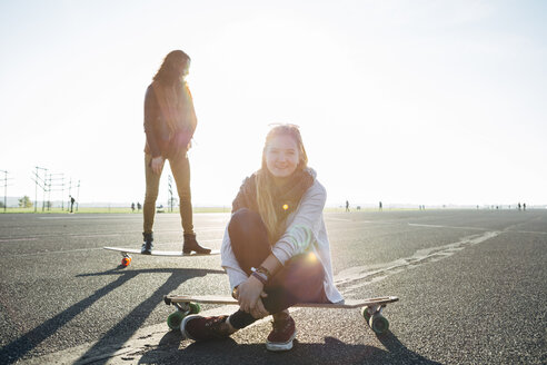 Germany, Berlin, Tempelhof Field, two young women with longboards on runway at backlight - FX000090