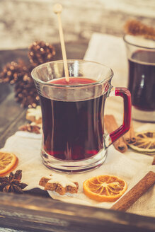 Glasses of mulled wine, orange slices and cinnamon stars on cloth and wooden tray - SARF000982
