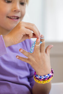 Little girl making loom bracelets - JFEF000530
