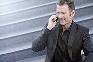 Well dressed businessman sitting on steps telephoning with smartphone - GUFF000039