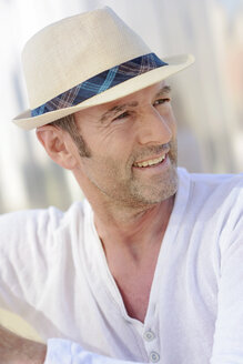 Portrait of smiling mature man with stubble wearing summer hat - GUFF000050