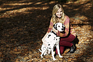 Smiling blond woman with Dalmatian in autumnal forest - GDF000544