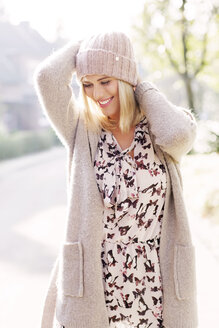 Smiling blond woman wearing patterned dress, cardigan and wool cap - GDF000548