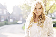 Portrait of smiling blond woman at backlight - GDF000563