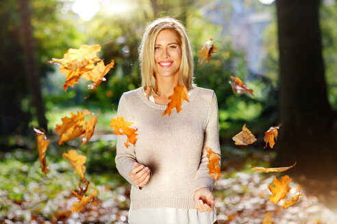 Portrait of smiling blond woman throwing with autumn leaves - GDF000568