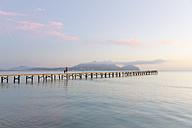 Spain, Balearic Islands, Majorca, people waklking on a jetty in the morning light - MSF004334