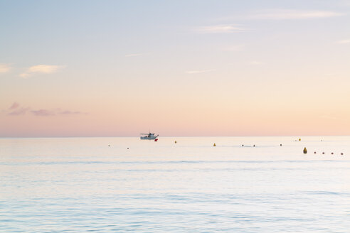 Spain, Balearic Islands, Majorca, Three people swimming in the sea in the morning light - MSF004339
