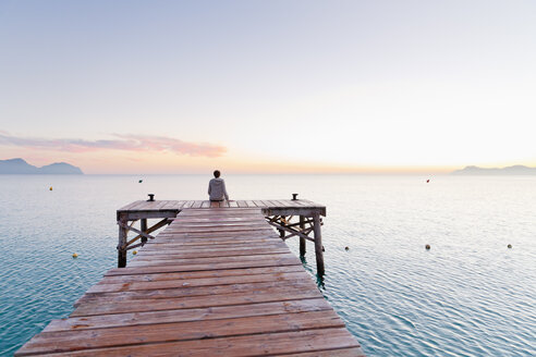Spain, Balearic Islands, Majorca, one teenage boy sitting on a jetty in the morning - MSF004342