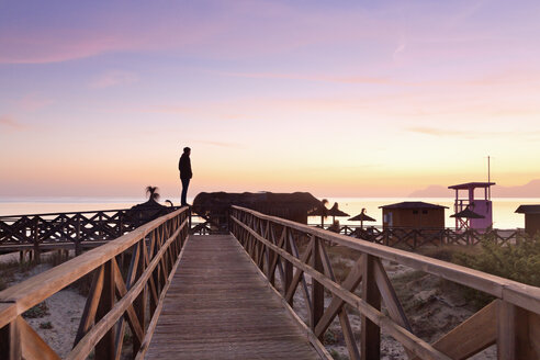 Spain, Balearic Islands, Majorca, one teenage boy standing on a wooden railing watching the sea - MSF004349