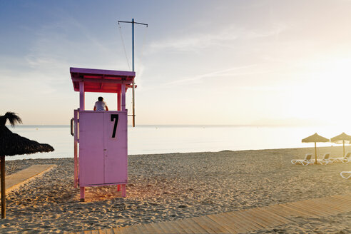Spain, Balearic Islands, Majorca, one teenage boy standing on a lifeguard stand watching the sea - MSF004354