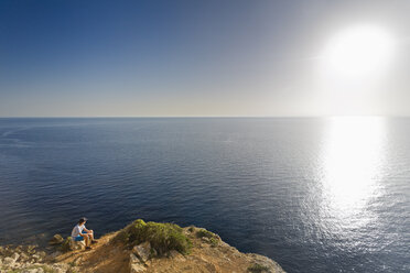 Spain, Balearic Islands, Majorca, one teenage boy sitting on a rock at the cliff coast, watching the sundown - MSF004356