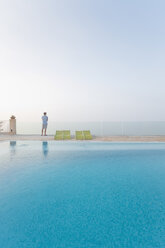 Spain, Balearic Islands, Majorca, one teenage boy standing on a safty glass rail at a swimmingpool - MSF004375
