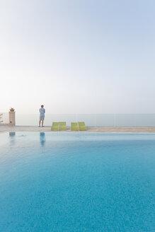 Spain, Balearic Islands, Majorca, one teenage boy standing on a safty glass rail at a swimmingpool - MSF004375