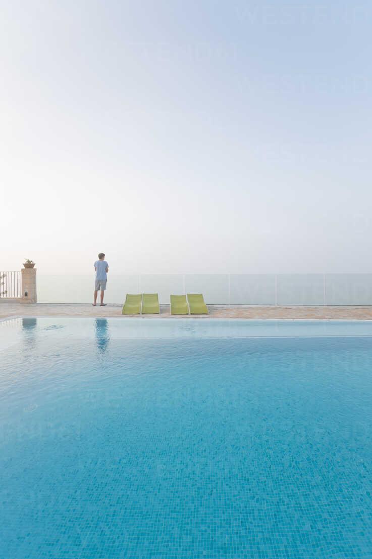 Spain, Balearic Islands, Majorca, one teenage boy standing on a safty glass rail at a swimmingpool - MSF004375 - Mel Stuart/Westend61