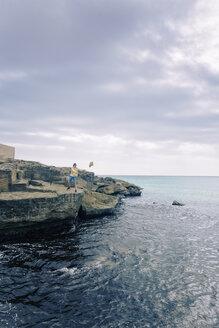 Spain, Balearic Islands, Majorca, one teenage boy throwing a rock into the sea - MSF004363
