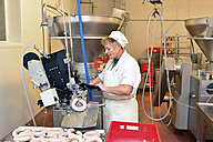 Woman working at sausage production in a butchery - LYF000317