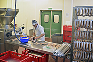Woman working at sausage production in a butchery - LYF000318