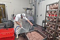 Man cleaning container with sausage meat in a butchery - LYF000321