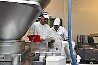 Two men talking in a butchery - LYF000346