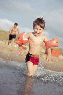 Smiling little boy running with his water wings into the sea - MVC000138