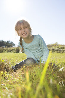 Smiling girl sitting on a meadow - OJF000061
