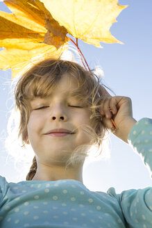 Portrait of girl with closed eyes holding autumn leaves - OJF000064