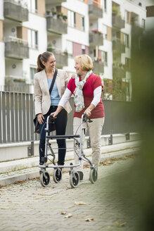 Adult granddaughter assisting her grandmother walking with wheeled walker - UUF002531