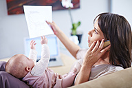 Mother with baby on couch talking on cell phone and looking at papers - ZEF002286