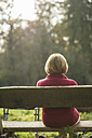 Senior woman sitting on a park bench, back view - UUF002576