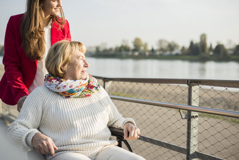 Granddaughter assisting her grandmother sitting in wheelchair - UUF002602