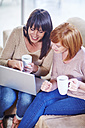 Two happy women sitting on couch with laptop and cups - ZEF002305