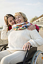 Young woman head to head with her laughing grandmother sitting in wheelchair - UUF002610