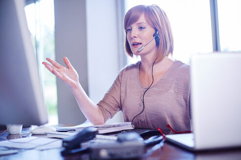 Woman at desk wearing a headset - ZEF002315