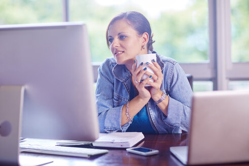 Smiling woman at desk holding a coffee cup - ZEF002323