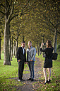 Young businesswoman photographing  business partners with her smartphone in a park - PAF001074