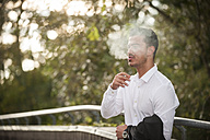 Stylish young man smoking a cigarette - PAF001075
