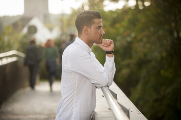 Stylish young man leaning on railing of a footbridge - PAF001077