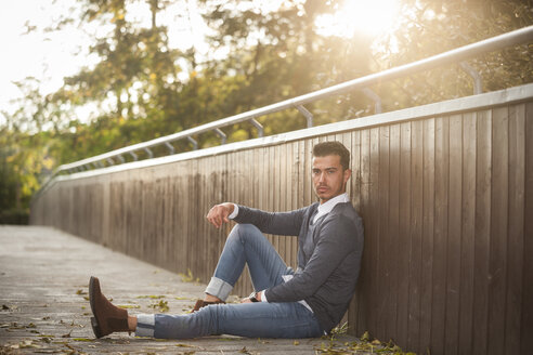 Stylish young man sitting on a footbridge - PAF001079