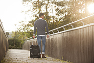 Young man walking with his wheeled luggage on a footbridge at backlight - PAF001087
