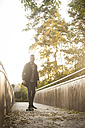 Young man skateboarding on a footbridge at backlight - PAF001088