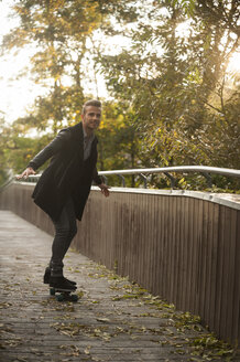 Smiling young man skateboarding on a footbridge in autumn - PAF001089