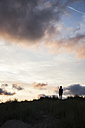 Silhouette of teenage boy standing on beach dune in front of evening twilight - MVC000141