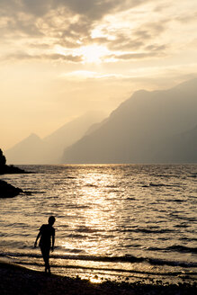 Italy, Veneto, Malcesine, Boy standing at Lake Garda in evening light - LVF002168
