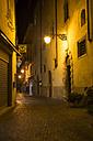 Italy, Veneto, Malcesine, Lane at Palazzo dei Capitani at night - LVF002161