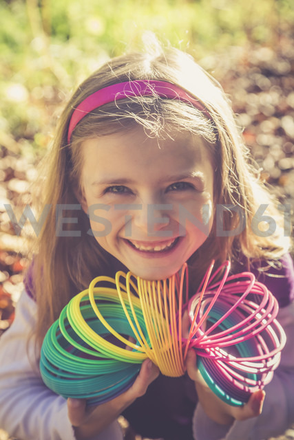 Portrait of smiling little girl with spiral in prismatic colours - SARF001001