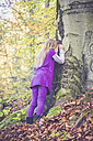 Little girl leaning at treetrunk with closed eyes playing hide and seek - SARF001002