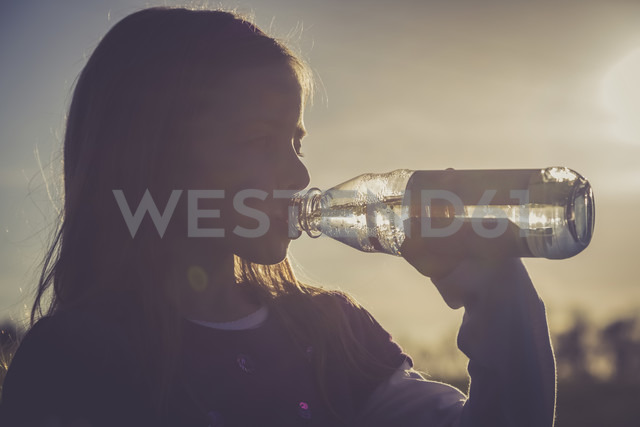 Girl drinking water out of a water bottle at backlight - SARF001021