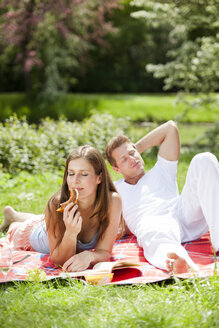 Happy couple having a picnic in park - CvK000200